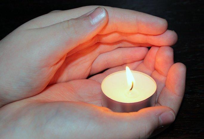 manos sosteniendo una vela y recibiendo el calor por radiacion