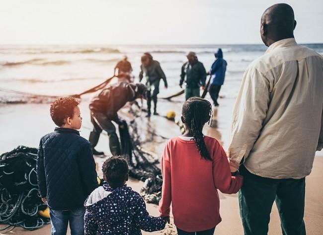 niños con hombre adulto frente al mar