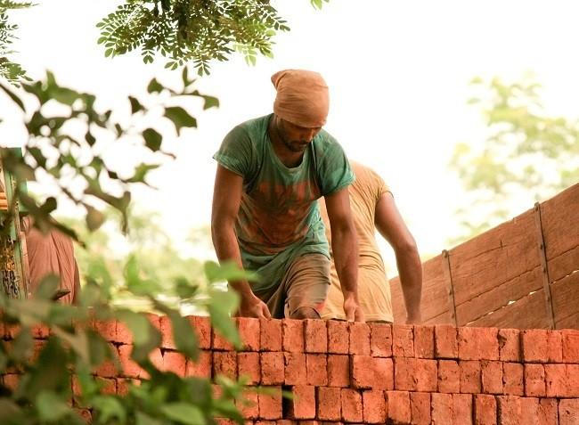 trabajador construyendo muro de ladrillos