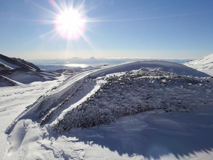 paisaje de una montaña con nieve con el sol