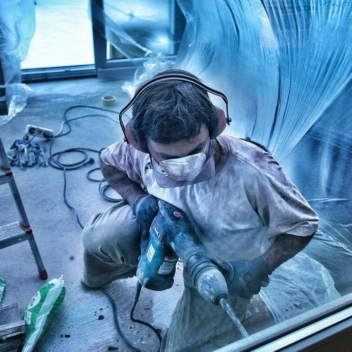 contaminacion sonora hombre trabajando con un taladro y con proteccion de orejas